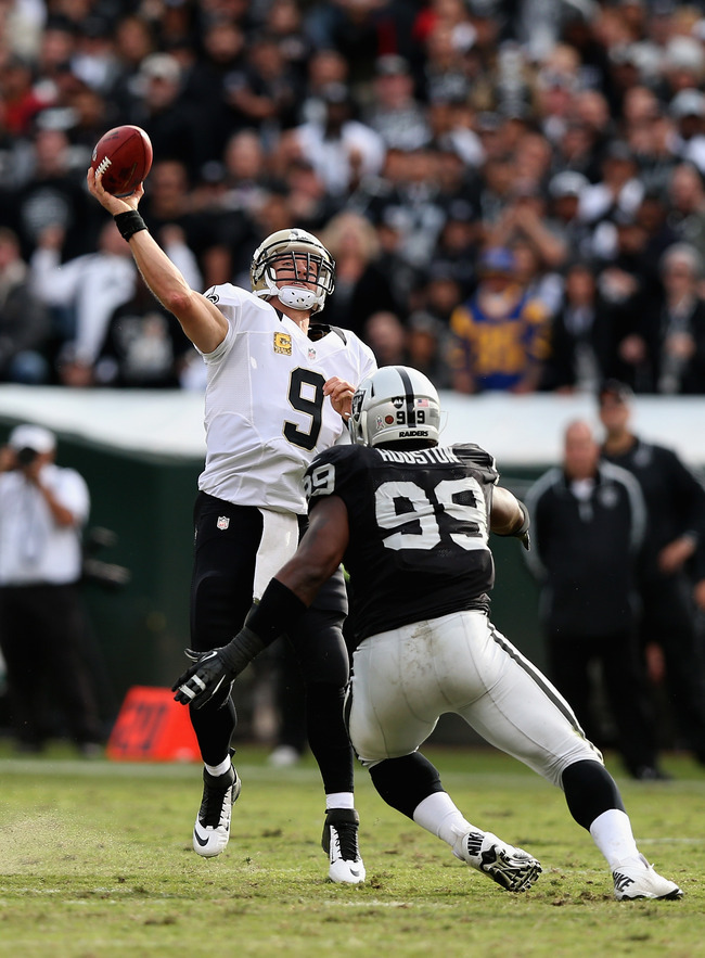 OAKLAND, CA - NOVEMBER 18:  Drew Brees #9 of the New Orleans Saints threws a long touchdown pass to Lance Moore #16 in the second period before being hit by Lamarr Houston #99 of the Oakland Raiders at O.co Coliseum on November 18, 2012 in Oakland, Califo