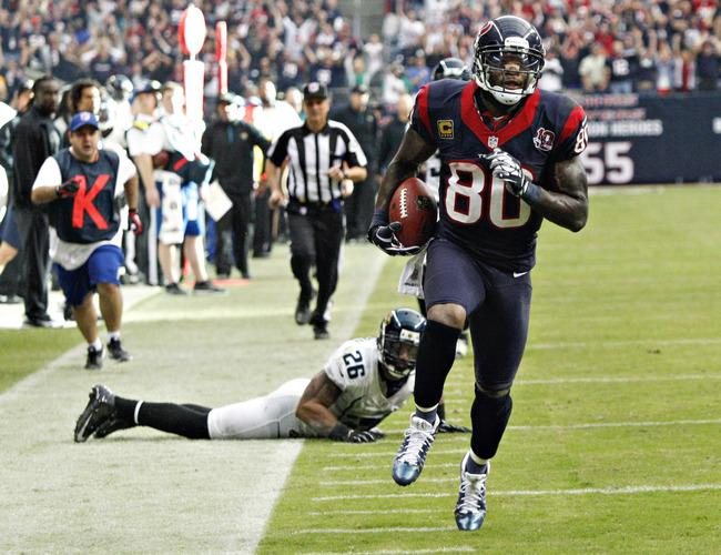 HOUSTON, TX - NOVEMBER 18:  Andre Johnson #80 of the Houston Texans scores on a 48 yard reception in overtime against the Jacksonville Jaguars as Dawan Landry #26 of the Jacksonville Jaguars watches at Reliant Stadium on November 18, 2012 in Houston, Texa