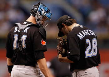 ST PETERSBURG, FL - JUNE 09:  Pitcher Shaun Marcum #28 (right) and catcher John Buck #14 of the Toronto Blue Jays chat at the mound against the Tampa Bay Rays during the game at Tropicana Field on June 9, 2010 in St. Petersburg, Florida.  (Photo by J. Mer