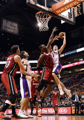 PHOENIX, AZ - NOVEMBER 17:  Goran Dragic #1 of the Phoenix Suns loses the ball as he attempts a shot against Chris Bosh #1 of the Miami Heat during the NBA game at US Airways Center on November 17, 2012 in Phoenix, Arizona.  The Heat defeated the Suns 97-