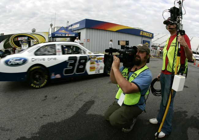 LOUDON, NH - SEPTEMBER 13:  ESPN film crew members capture David Gilliland, driver of the #38 Ford Drive One Ford leaving the garage area, at the beginning of practice for the NASCAR Sprint Cup Series Sylvania 300 at New Hampshire Motor Speedway on Septem