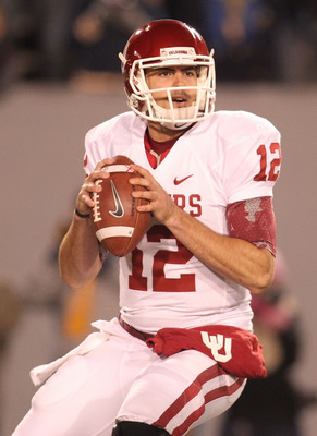 November 17, 2012; Morgantown, WV, USA; Oklahoma Sooners quarterback Landry Jones (12) looks to pass against the West Virginia Mountaineers during the third quarter at Milan Puskar Stadium. The Oklahoma Sooners won 50-49. Mandatory Credit: Charles LeClair