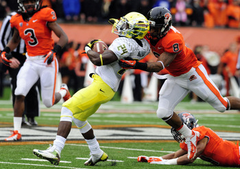 CORVALLIS, OR - NOVEMBER 24: Running back Kenjon Barner #24 of the Oregon Ducks is tackled by safety Tyrequek Zimmerman #8 of the Oregon State Beavers in the first quarter of the game on November 24, 2012 at Reser Stadium in Corvallis, Oregon. (Photo by S