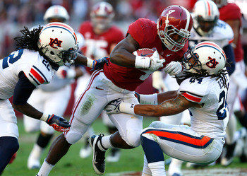 TUSCALOOSA, AL - NOVEMBER 24:  T.J. Yeldon #4 of the Alabama Crimson Tide rushes over T'Sharvan Bell #22 and Ryan Smith #24 of the Auburn Tigers at Bryant-Denny Stadium on November 24, 2012 in Tuscaloosa, Alabama.  (Photo by Kevin C. Cox/Getty Images)