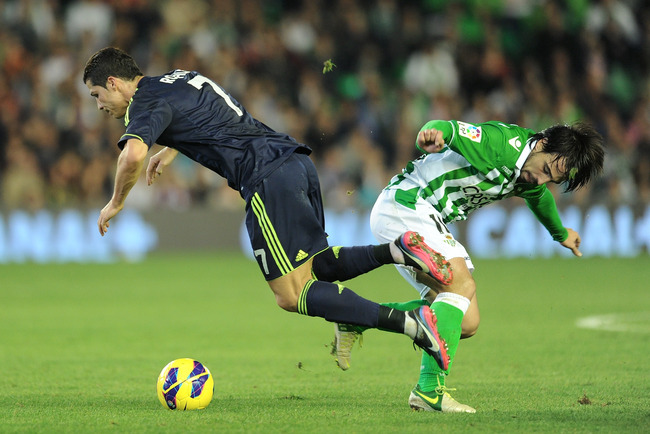 SEVILLE, SPAIN - NOVEMBER 24: Cristiano Ronaldo (R) of Real Madrid CF is tackled by Benat Etxebarria of Real Betis Balompie during the La Liga match between Real Betis Balompie and Real Madrid CF at Estadio Benito Villamarin on November 24, 2012 in Sevill