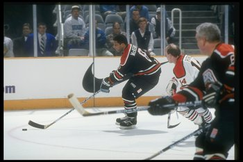 Tony McKegney reaching for the puck.