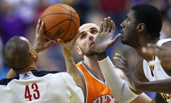 Marcin Gortat (center) prepares for the opening tipoff against Indiana Pacers center Roy Hibbert (right)