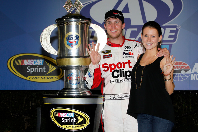 HAMPTON, GA - SEPTEMBER 02:  Denny Hamlin, driver of the #11 Sport Clips Toyota, and his girlfriend Jordan Fish celebrate with the trophy in victory lane during the NASCAR Sprint Cup Series AdvoCare 500 at Atlanta Motor Speedway on September 2, 2012 in Ha