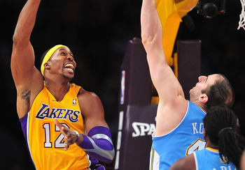November 30, 2012; Los Angeles, CA, USA; Los Angeles Lakers center Dwight Howard (12) goes for a basket against the defense of Denver Nuggets center Kosta Koufos (41) during the first half at Staples Center. Mandatory Credit: Gary A. Vasquez-US PRESSWIRE