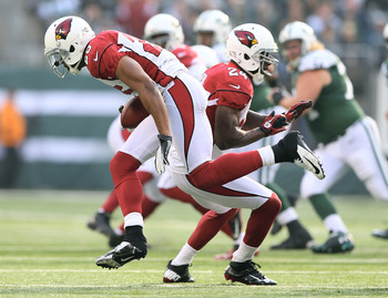 Adrian Wilson blocks for Kerry Rhodes after an INT Sunday.