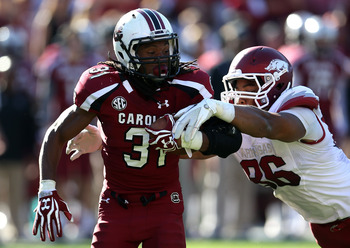COLUMBIA, SC - NOVEMBER 10:  Trey Flowers #86 of the Arkansas Razorbacks tries to tackle Kenny Miles #31 of the South Carolina Gamecocks during their game at Williams-Brice Stadium on November 10, 2012 in Columbia, South Carolina.  (Photo by Streeter Leck