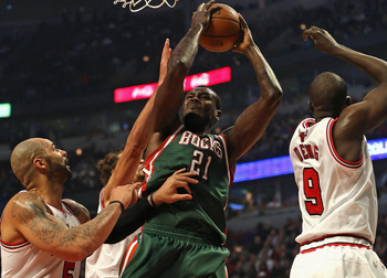 CHICAGO, IL - NOVEMBER 26: Samuel Dalembert #21 of the Milwaukee Bucks shoots between Carlos Boozer #5 and Loul Deng #9 of the Chicago Bulls at the United Center on November 26, 2012 in Chicago, Illinois. The Bucks defeated the Bulls 93-92. NOTE TO USER: