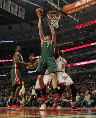 CHICAGO, IL - NOVEMBER 26: Ersan Ilyasova #7 of the Milwaukee Bucks rebounds over Loul Deng #9 and Carlos Boozer #5 of the Chicago Bulls at the United Center on November 26, 2012 in Chicago, Illinois. The Bucks defeated the Bulls 93-92. NOTE TO USER: User