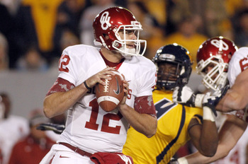 MORGANTOWN, WV - NOVEMBER 17:  Landry Jones #12 of the Oklahoma Sooners drops back to pass against the West Virginia Mountaineers during the game on November 17, 2012 at Mountaineer Field in Morgantown, West Virginia.  (Photo by Justin K. Aller/Getty Imag