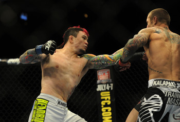 June 8, 2012; Sunrise, FL, USA; Scott Jorgensen (left) hits Eddie Wineland during UFC bout at BankAtlantic Center. Mandatory Credit: Steve Mitchell-USA TODAY Sports