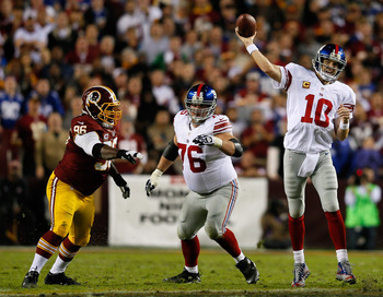 LANDOVER, MD - DECEMBER 03:  Quarterback  Eli Manning #10 of the New York Giants throws the ball as teammate Chris Snee #76 blocks Barry Cofield #96 of the Washington Redskins in the first half at FedExField on December 3, 2012 in Landover, Maryland.  (Ph