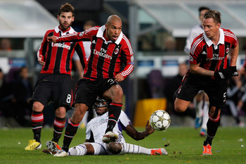 ANDERLECHT, BELGIUM - NOVEMBER 21:  Dieudonne Mbokani of Anderlecht tackles Nigel De Jong of AC Milan during the UEFA Champions League Group C match between RSC Anderlecht and AC Milan at the Constant Vanden Stock Stadium on November 21, 2012 in Anderlech