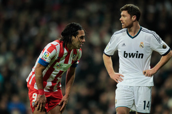 MADRID, SPAIN - DECEMBER 01:  Radamel Falcao (L) of Club Atletico de Madrid rests close to Xabi Alonso (R) of Real Madrid during the La Liga match between Real Madrid CF and Club Atletico de Madrid at Estadio Santiago Bernabeu on December 1, 2012 in Madri