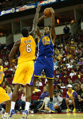 Los Angeles Lakers forward Earl Clark (left) defends Golden State Warriors forward Jeremy Tyler (right)