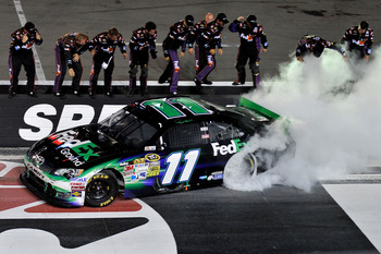 BRISTOL, TN - AUGUST 25:  Denny Hamlin, driver of the #11 FedEx Ground Toyota, celebrates with a burnout after winning the NASCAR Sprint Cup Series IRWIN Tools Night Race at Bristol Motor Speedway on August 25, 2012 in Bristol, Tennessee.  (Photo by Jason