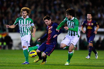 ,SEVILLE, SPAIN - DECEMBER 09:  Lionel Messi of FC Barcelona (C) duels for the ball with Benat Etxeberria (R) and Jose Alberto Canas of Real Betis Balompieduring the La Liga match between Real Betis Balompie and FC Barcelona at Estadio Benito Villamarin o