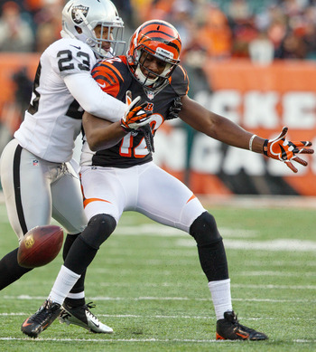Nov 25, 2012;  Cincinnati, OH, USA; Oakland Raiders defensive back Joselio Hanson (23) forces a fumble against Cincinnati Bengals wide receiver Mohamed Sanu (12) during the fourth quarter of the game at Paul Brown Stadium. Mandatory Credit: Rob Leifheit-U
