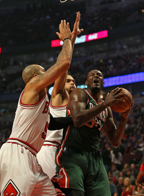 CHICAGO, IL - NOVEMBER 26:  Samuel Dalembert #21 of the Milwaukee Bucks shoots between Carlos Boozer #5 and Joakim Noah #13 of the Chicago Bulls at the United Center on November 26, 2012 in Chicago, Illinois. The Bucks defeated the Bulls 93-92. NOTE TO US