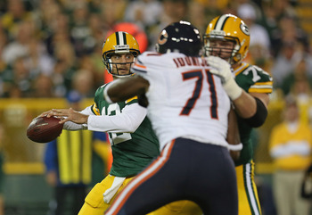 GREEN BAY, WI - SEPTEMBER 13:  Aaron Rodgers #12 of the Green Bay Packers passes as Bryan Bulaga #75 blocks Israel Idonije #71 of the Chicago Bears at Lambeau Field on September 13, 2012 in Green Bay, Wisconsin. The Packers defeated the Bears 23-10.  (Pho