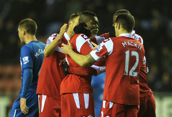 Djibril Cisse is congratulated by his team-mates after putting QPR 2-1 up at Wigan last Saturday