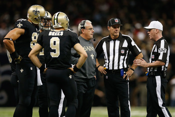 Referee John Parry explains a ruling to New Orleans Saints coaches and players.