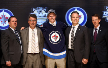 PITTSBURGH, PA - JUNE 22:  Jacob Trouba, ninth overall pick by the Winnipeg Jets, poses on stage with Jets representatives during Round One of the 2012 NHL Entry Draft at Consol Energy Center on June 22, 2012 in Pittsburgh, Pennsylvania.  (Photo by Bruce