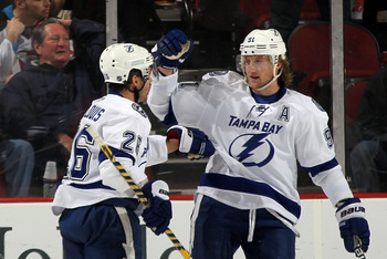 NEWARK, NJ - FEBRUARY 26:  Martin St. Louis #26 (L)of the Tampa Bay Lightning scores at 6:39 of the second period against the New Jersey Devils and is joined by Steven Stamkos #91 (R) at the Prudential Center on February 26, 2012 in Newark, New Jersey.  (