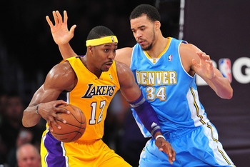 November 30, 2012; Los Angeles, CA, USA; Los Angeles Lakers center Dwight Howard (12) controls the ball against the defense of Denver Nuggets center JaVale McGee (34) during the first half at Staples Center. Mandatory Credit: Gary A. Vasquez-USA TODAY Spo