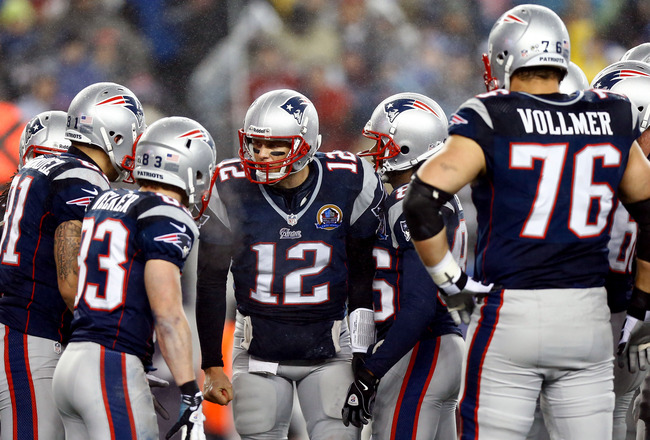FOXBORO, MA - DECEMBER 16:  Quarterback Tom Brady #12 of the New England Patriots talks with his team in a huddle against the San Francisco 49ers at Gillette Stadium on December 16, 2012 in Foxboro, Massachusetts.  (Photo by Jared Wickerham/Getty Images)