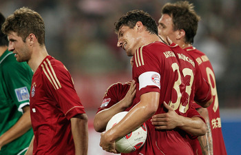 BEIJING, CHINA - JULY 24: Mario Gomez (R) of Bayern Muenchen celebrates with his team-mates after scoring during the pre-season friendly match between Beijing Guo'an and Bayern Muenchen at Beijing Workers Stadium on July 24, 2012 in Beijing, China. (Photo