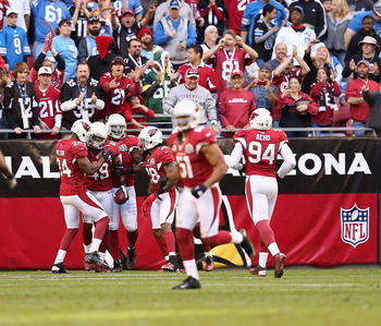 Johnson (with ball) celebrates his pick-six against the Lions.