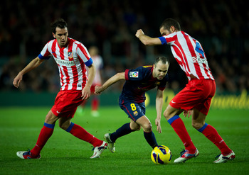 BARCELONA, SPAIN - DECEMBER 16: Andres Iniesta (C) of Barcelona duels for the ball with Diego Godin (L) and Mario Suarez of Club Atletico de Madrid   during the la Liga match between FC Barcelona and Club Atletico de Madrid at the Camp Nou stadium on Dece