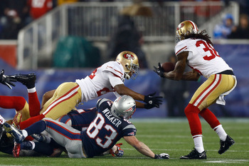 Safety Dashon Goldson (right) recovers a fumble in the third quarter and returns it for 66 yards.