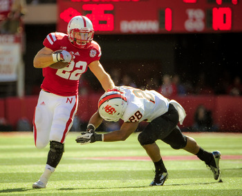 LINCOLN, NE - SEPTEMBER 22: Running back Rex Burkhead #22 of the Nebraska Cornhuskers stiff arms defensive back Cameron Gupton #28 of the Idaho State Bengals during their game at Memorial Stadium on September 22, 2012 in Lincoln, Nebraska. (Photo by Eric