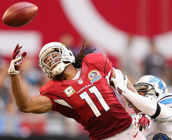 GLENDALE, AZ - DECEMBER 16:  Wide receiver Larry Fitzgerald #11 of the Arizona Cardinals is unable to make a leaping reception under pressure from cornerback Chris Houston #23 of the Detroit Lions during the NFL game at the University of Phoenix Stadium o