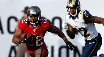 TAMPA, FL - DECEMBER 23: Running back Doug Martin #22 of the Tampa Bay Buccaneers runs the ball as defender Trumaine Johnson #22 of the St. Louis Rams trails during the game at Raymond James Stadium on December 23, 2012 in Tampa, Florida. (Photo by J. Mer
