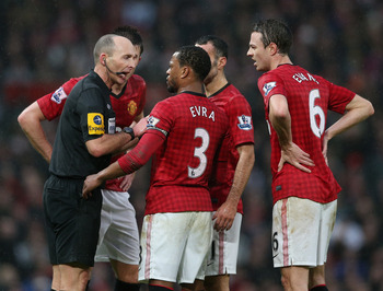 Referee Mike Dean is surrounded by Man United players after Newcastle's second goal.
