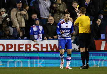 Reading striker Adam le Fondre is booked for his handball.