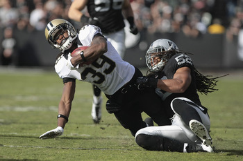 November 18, 2012; Oakland, CA, USA; Oakland Raiders outside linebacker Philip Wheeler (52) tackles New Orleans Saints running back Travaris Cadet (39) during the first quarter at O.co Coliseum. Mandatory Credit: Kelley L Cox-USA TODAY Sports