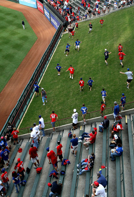 ARLINGTON, TX - OCTOBER 22:  Fans run on the grass to chase down home run balls hit during batting practice prior the Texas Rangers playing against the New York Yankees in Game Six of the ALCS during the 2010 MLB Playoffs at Rangers Ballpark in Arlington 