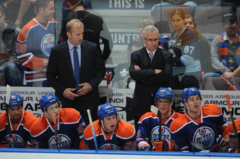 Ralph Krueger (left) and Tom Renney behind the Edmonton Oilers' bench.