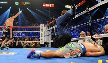 Juan Manuel Marquez celebrates in the background as Pacquiao lies motionless from a knockout that occurred in Round 6 of their fourth fight.