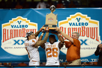 Dec 29, 2012; San Antonio, TX, USA; Texas Longhorns head coach Mack Brown (right) and safety Kenny Vaccaro (4) and running back D.J. Monroe (26) react after defeating the Oregon State Beavers in the Alamo Bowl at the Alamodome. Texas beat Oregon State 31-