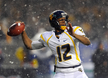 Dec 29, 2012; Bronx, NY, USA; West Virginia Mountaineers quarterback Geno Smith (12) drops back to pass during the second quarter against the Syracuse Orange at the 2012 New Era Pinstripe Bowl at Yankee Stadium.  Mandatory Credit: Rich Barnes-USA TODAY Sp