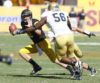 October 27, 2012; Tempe, AZ, USA; Arizona State Sun Devils quarterback Taylor Kelly (10) avoids the UCLA Bruins defensive end Datone Jones (56) during the first half at Sun Devil Stadium.  Mandatory Credit: Rick Scuteri-USA TODAY Sports